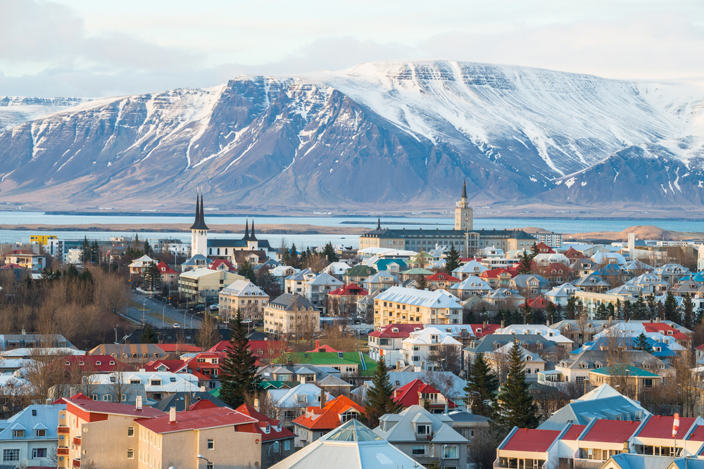a picture of Reykjavik with various colored buildings and a distant snow covered mountain across the river