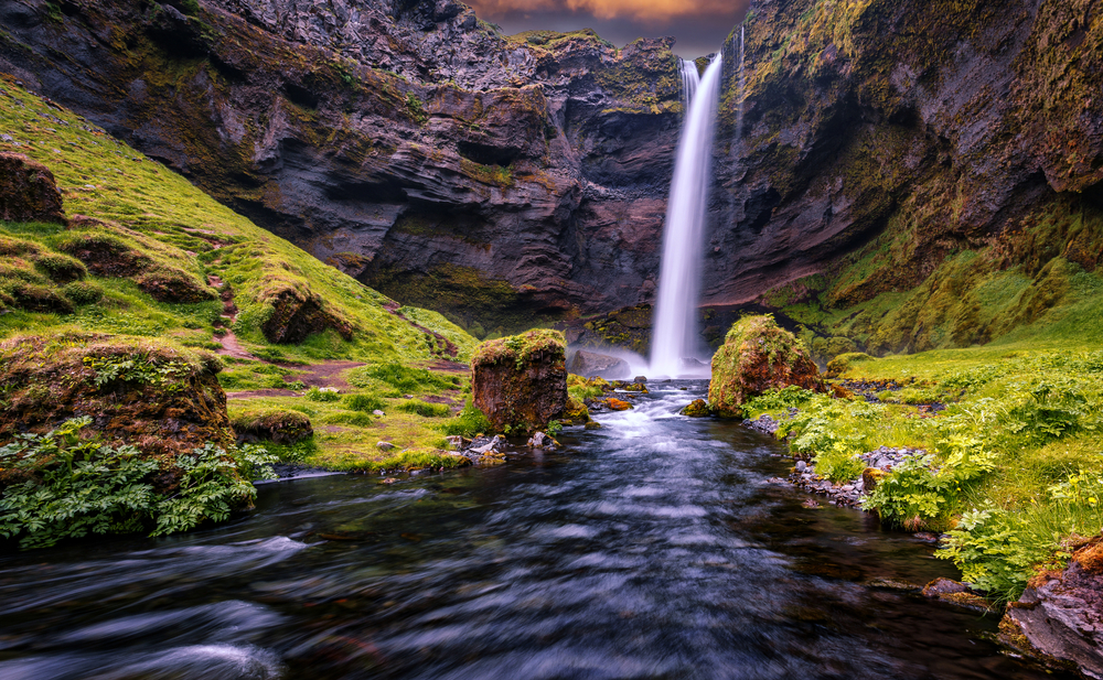 waterfall flowing into a river below surrounded by large rocks and green grass at sunset one of the best hiking trails in Iceland