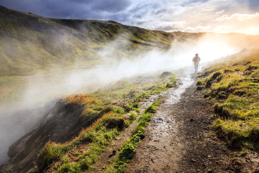 person shrouded in mist hiking in Iceland upriver at a hot spring