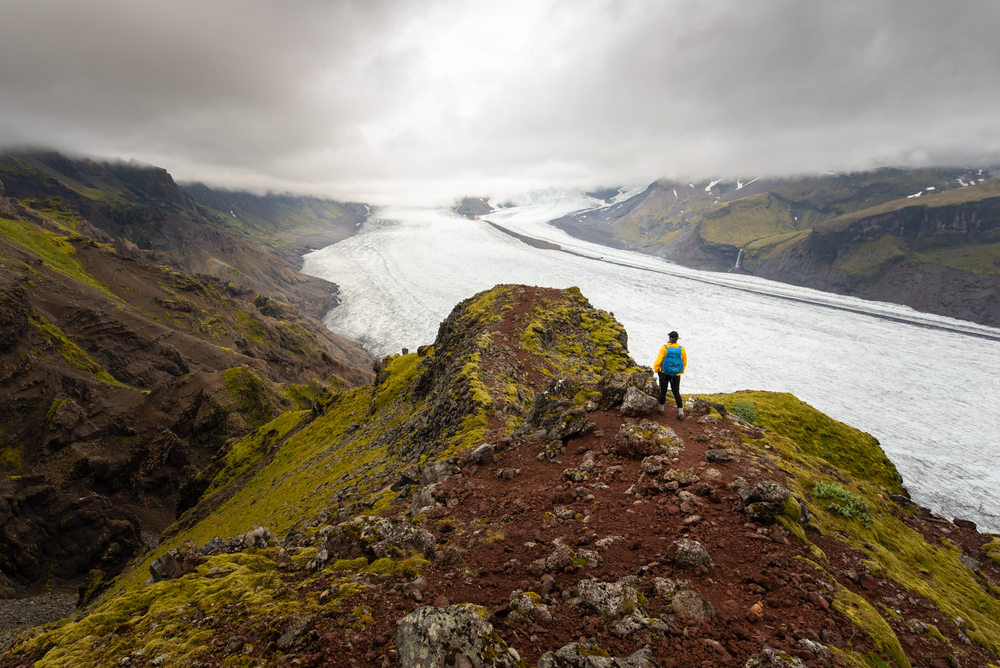 person after one of the hikes in iceland overlooking a glacier