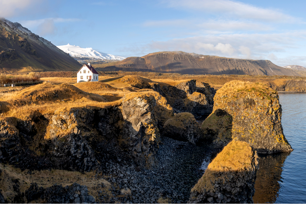 a white house with a red roof on the coast of iceland at sunset
