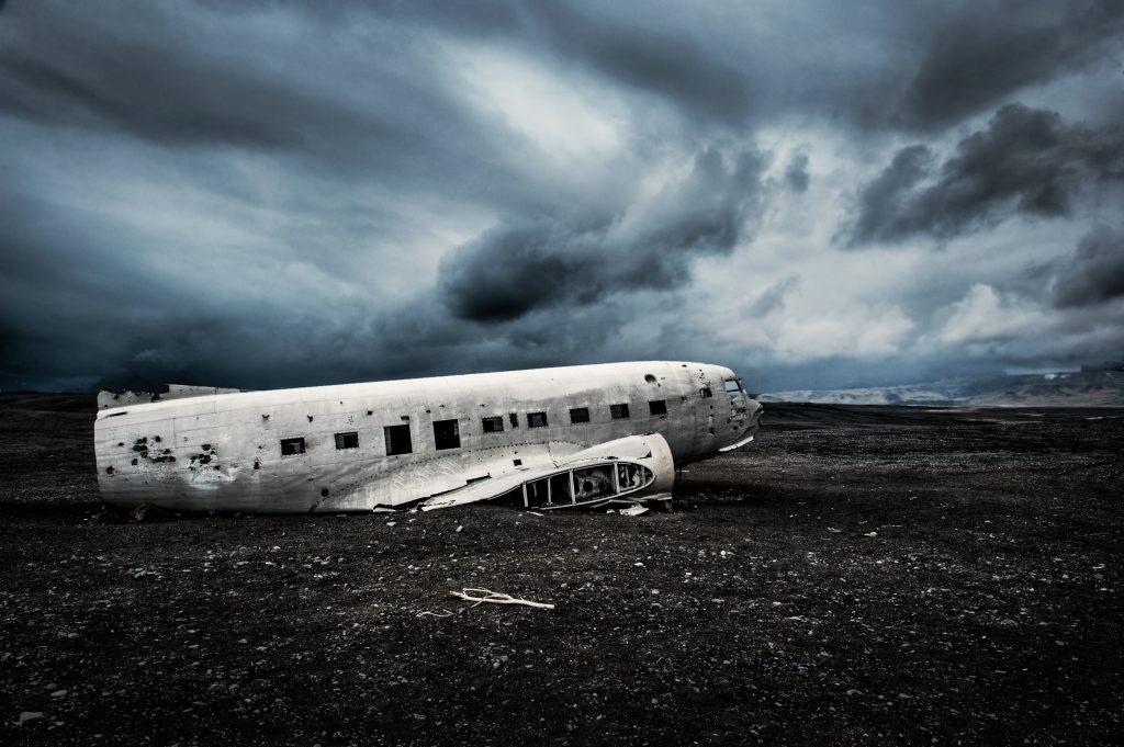 crashed air plane on a black sand beach in iceland on a moody day
