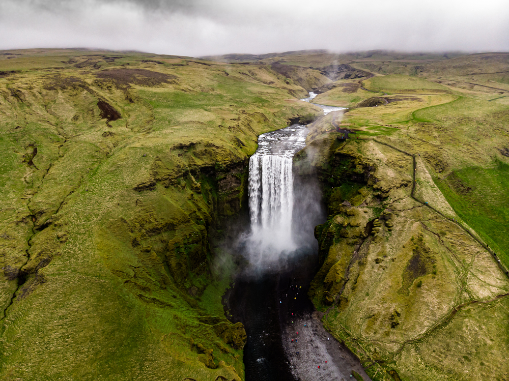 aerial image of a large waterfall in iceland surrounded by moss covered rocks