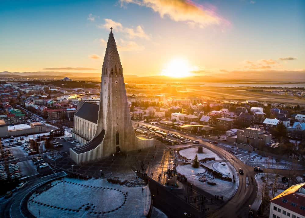 aerial shot of a large church in the center of Reykjavik at sunset with some snow on the ground in Iceland in November