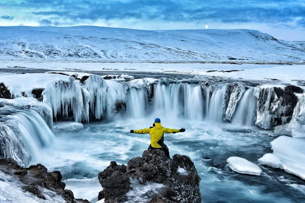 Mani n yellow jacket with his arms spread out sitting on a rock, looking at a waterfall surrounded by snow and ice in december in iceland
