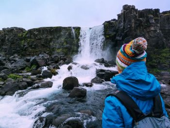 person standing in front of waterfall in iceland in november