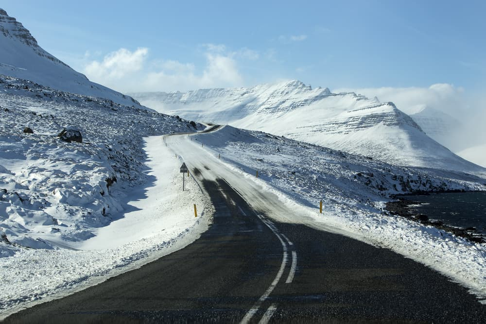 partially cleared road from snow on a sunny winter day with snow covered mountains in the distance in Iceland in November