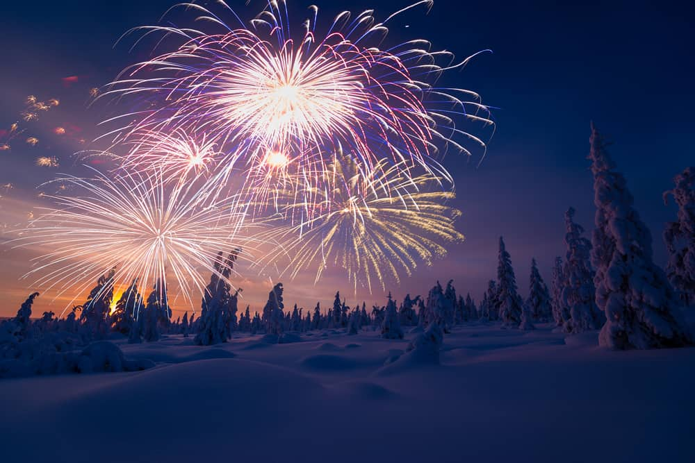 fireworks for New Years Eve with snow covered trees at twilight