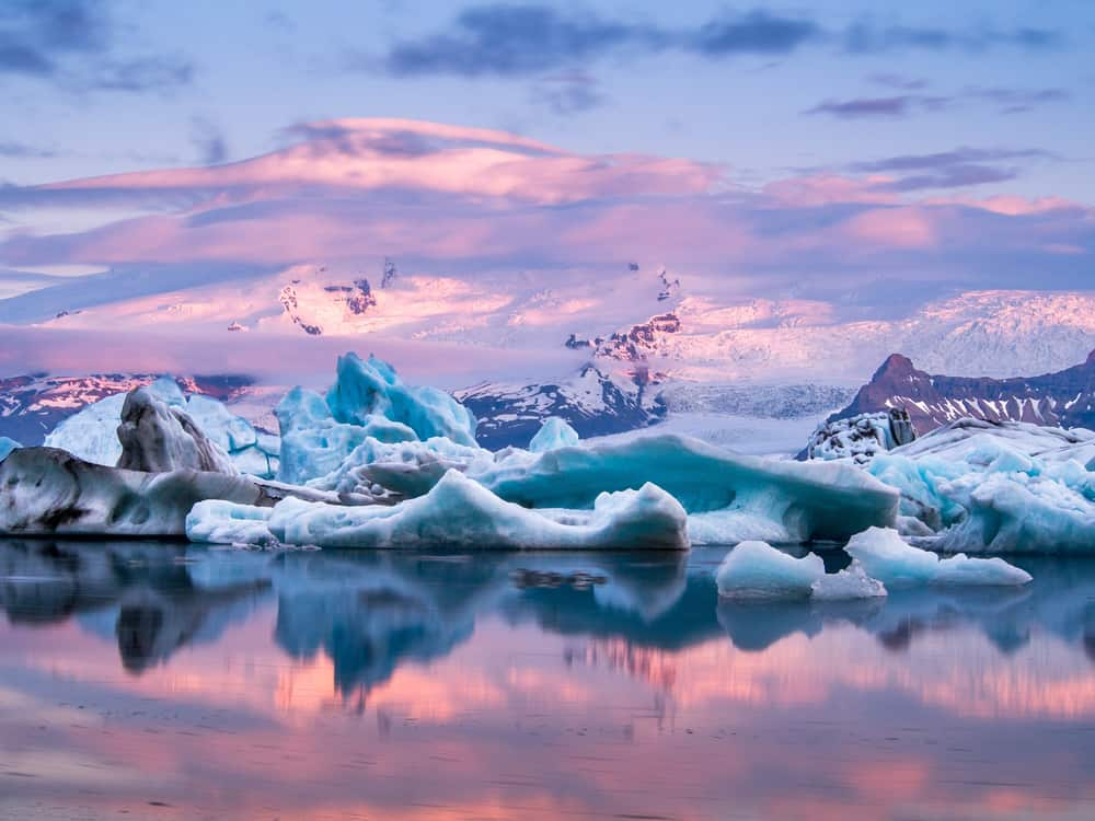 Glacier Lagoon with large icebergs and distant snow capped mountains at sunset in Iceland in December