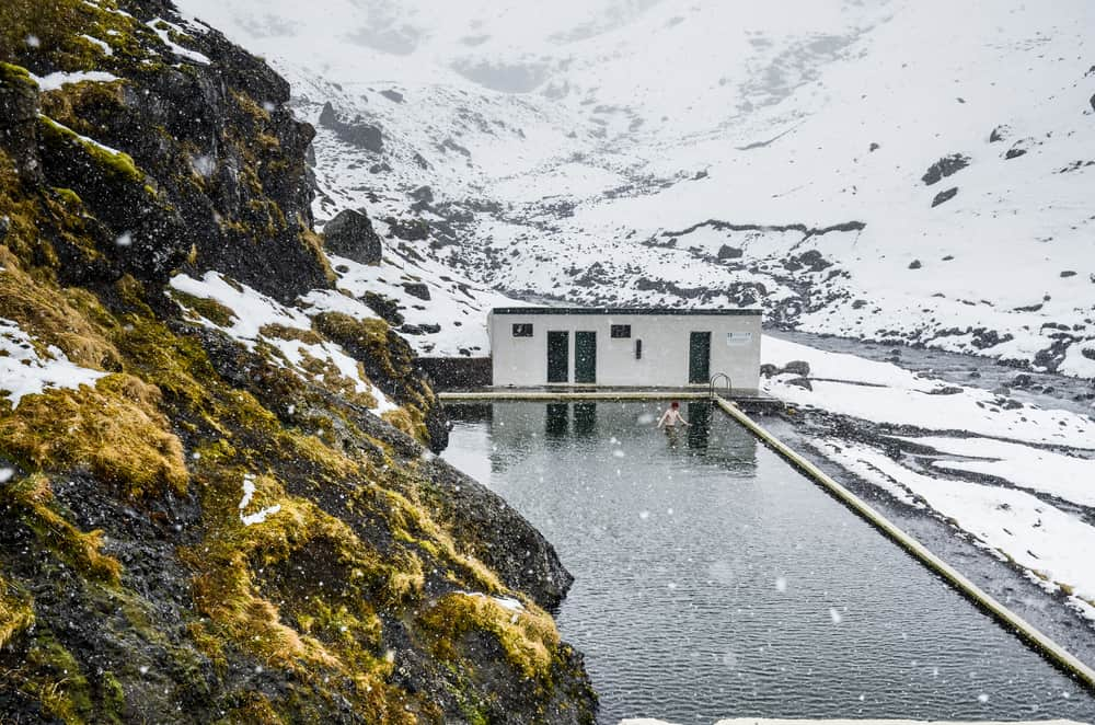 a man waist deep in a hot spring pool on a snowy moody day.