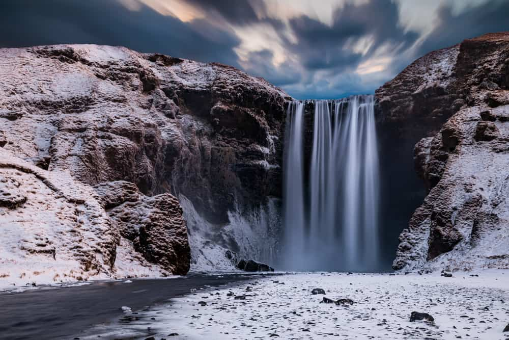 Skogafoss waterfall in Iceland on a moody winter day with snow on the ground