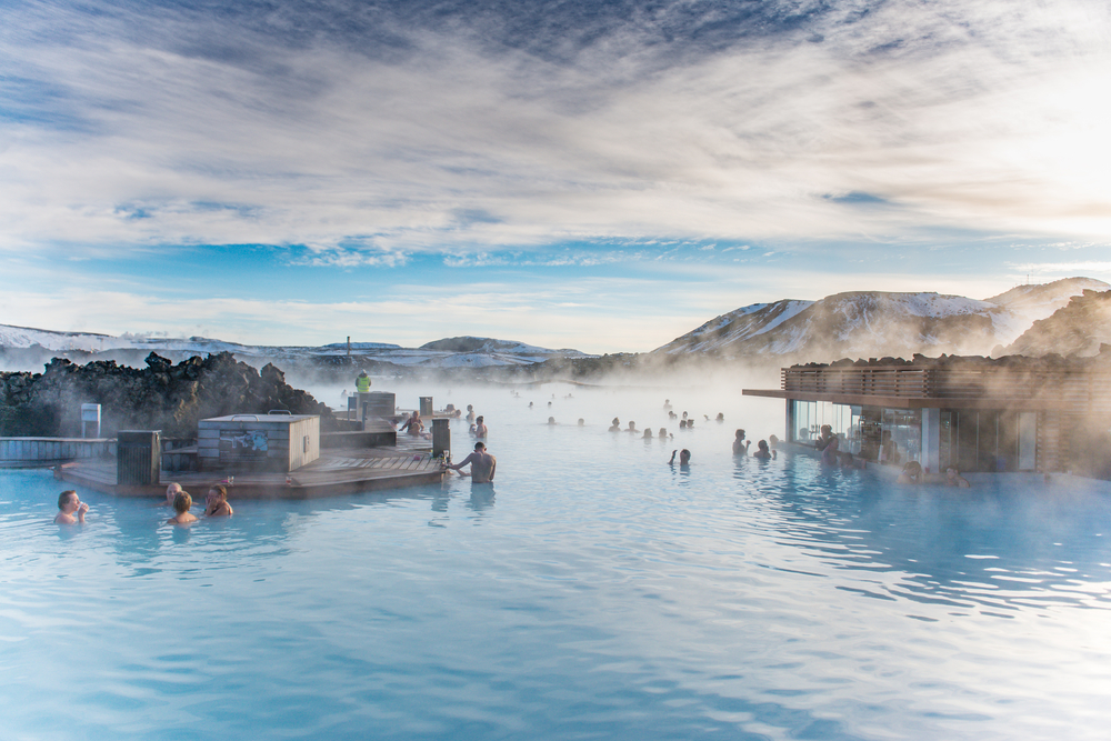 people swimming and relaxing on a sunny day in the blue lagoon in iceland in march