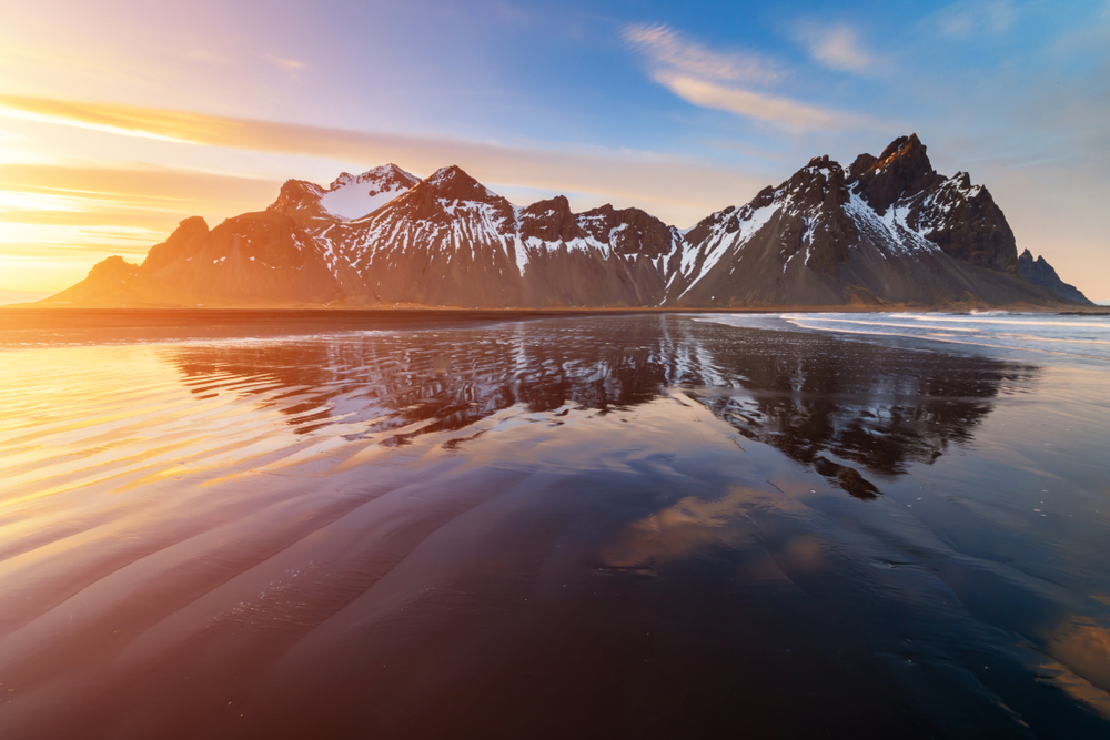 sunrise on a black sand beach with a large mountain and its reflection in the water during Iceland in March