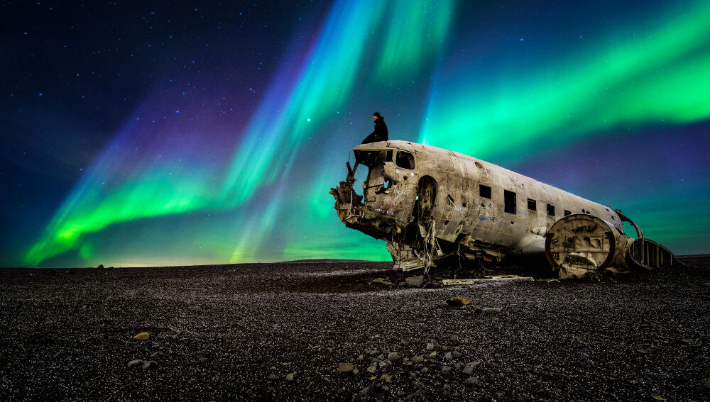 northern lights over the Iceland plane wreck with person sitting on it