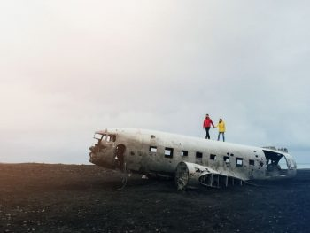 two tourists walking on top of the Solheimasandur plane wreck in Iceland