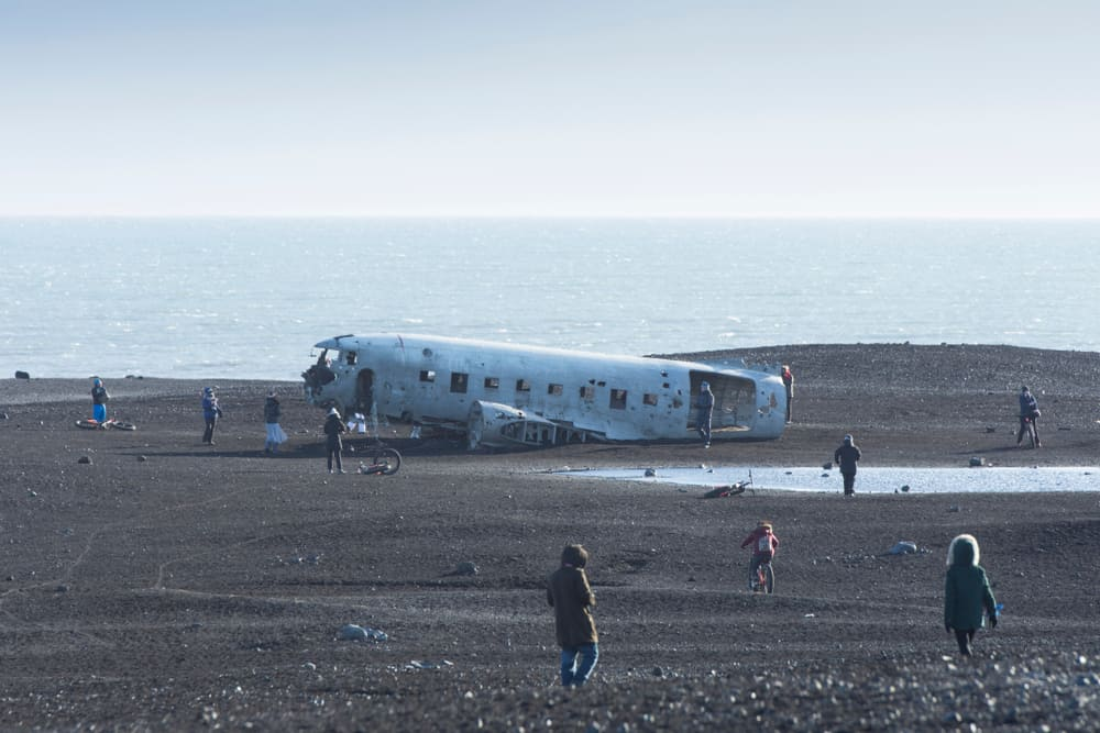 tourists walking around the Iceland plane wreck Solheimasandur
