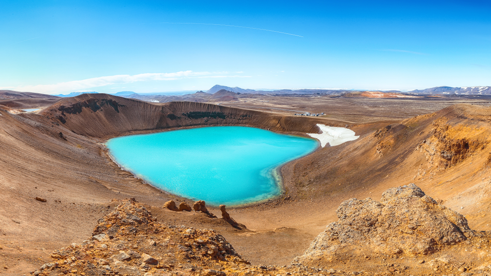 A volcanic crater and landscape. The crater is full of crystal blue water. The dirt around it is a dark yellowish orange and there are several small rock formations.