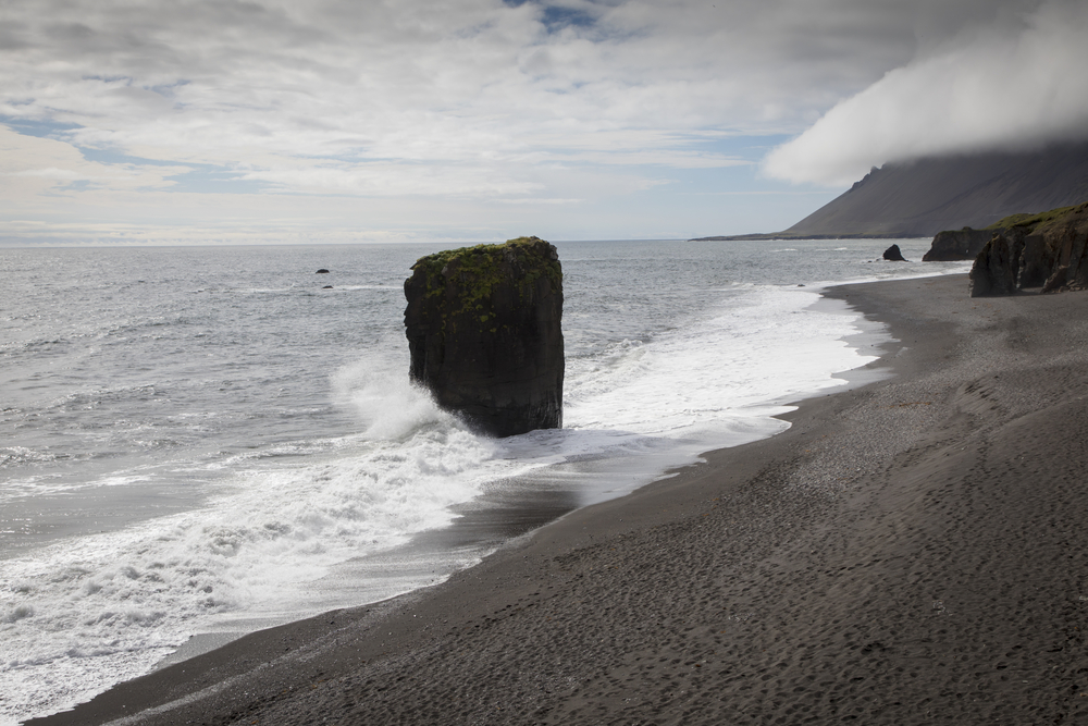 A black sand beach with rock formations on the beach and in the water. There is a large rectangular rock formation right where the waves crash that has moss on it. In the distance you can see the slope of a mountain.
