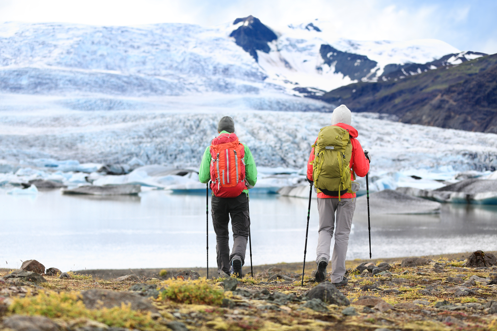 tourists in cold weather clothes and hiking gear near the glacier lagoon
