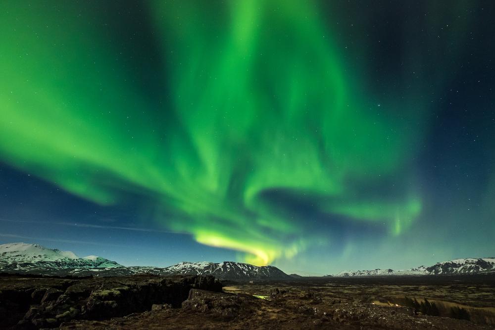 Northern Lights dancing over the vast landscape of Thingvellir National Park