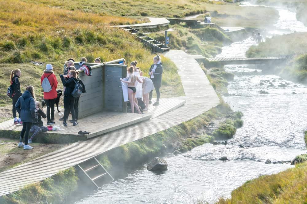 people on wood changing platforms at Reykjadalur Hot Springs