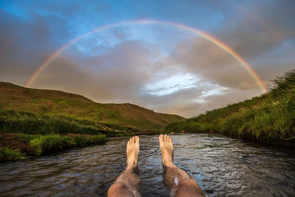 mans feet as he sits in a river looking at a rainbow while bathing at Reykjadalur Hot Springs