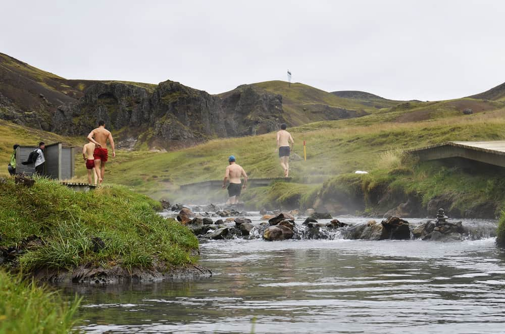 people walk upriver to bathe at Reykjadalur Hot Springs
