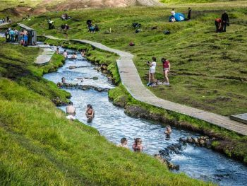 people swimming in Reykjadalur Hot Springs thermal river in iceland with green grass