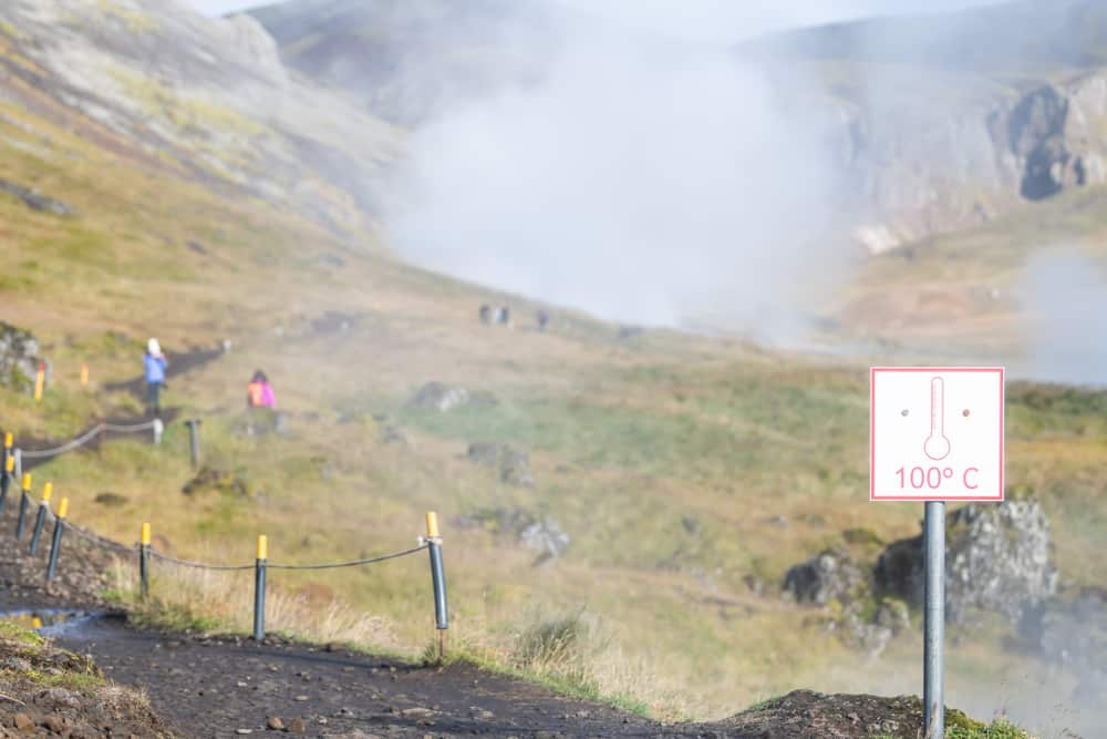 signs indicate water too hot at 100 degrees Celsius to touch along Reykjadalur Hot Springs hike