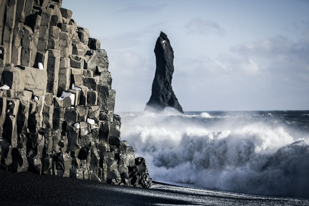 A black sand beach with a geometric rock formation on the beach. In the ocean you can see a large standing black rock formation. There are waves crashing on the shore. One of the best stops on an Iceland road trip.