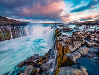 A large horse shoe shaped waterfall in Iceland. it is full of rocks and cascades over the entire edge of the horse shoe. It flows down into a river. The water is crystal blue and the sky is blue, pink, and purple with clouds. One of the best stops on an Iceland road trip