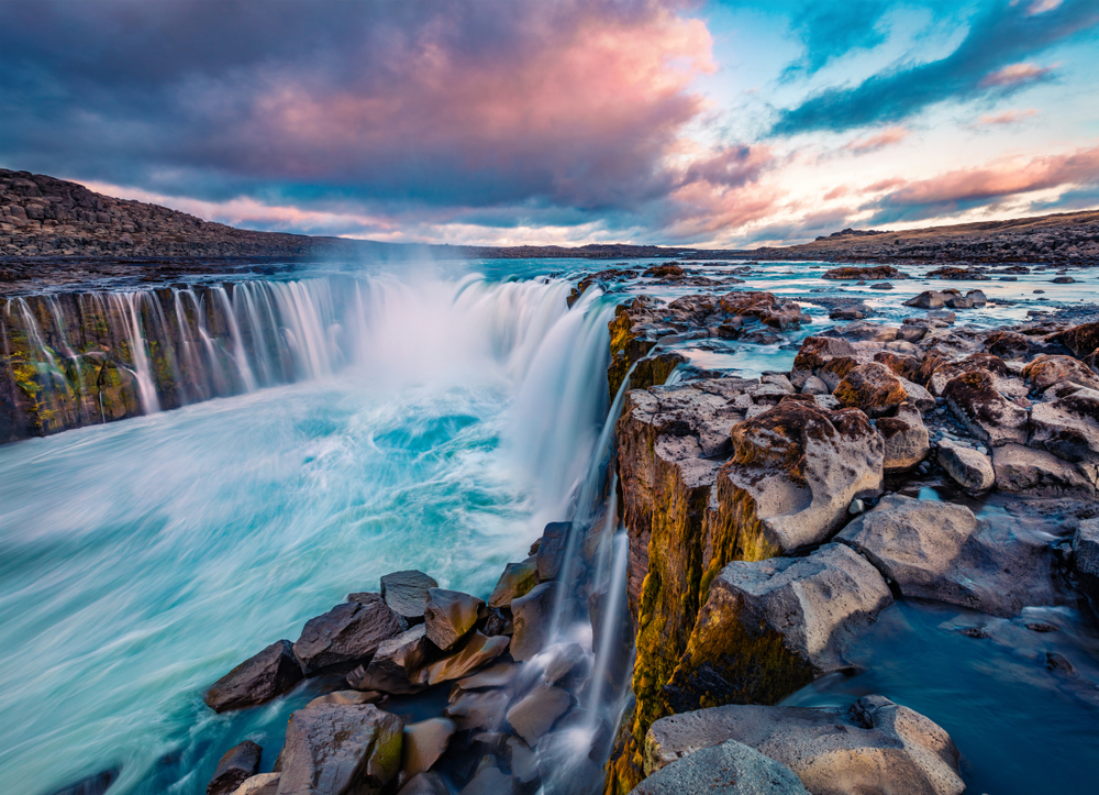 A large horse shoe shaped waterfall in Iceland. it is full of rocks and cascades over the entire edge of the horse shoe. It flows down into a river. The water is crystal blue and the sky is blue, pink, and purple with clouds.