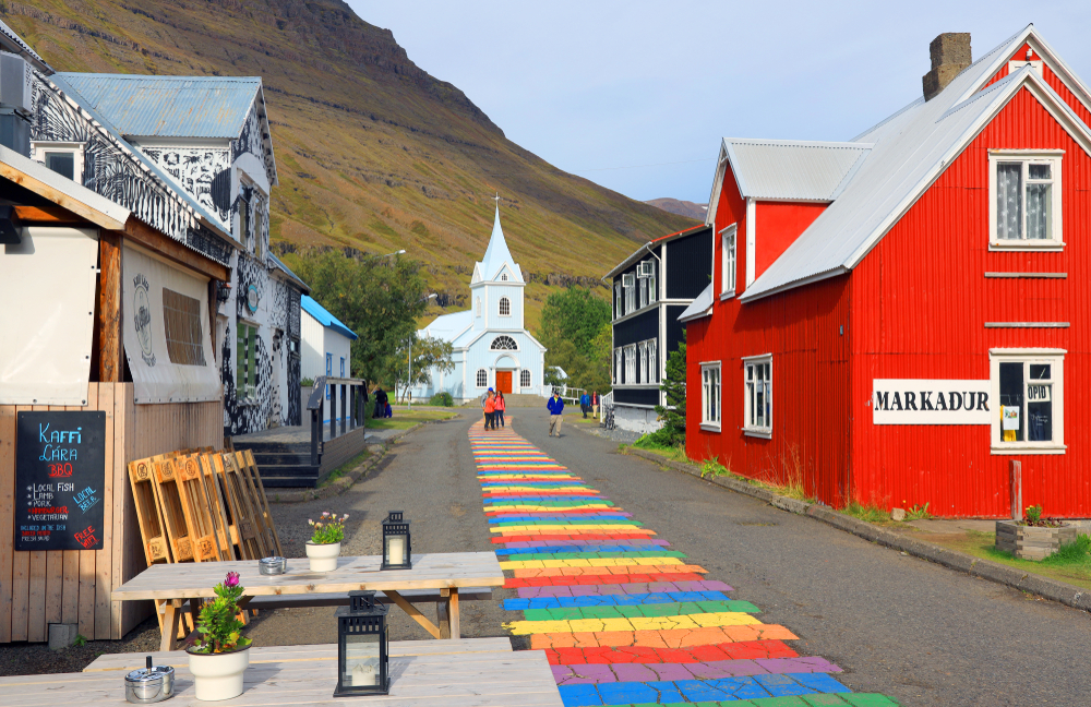 A street in a small town in Iceland. Down the street there is a rainbow painting, small shops, and a white church. Behind the church you can see the slope of a mountainside.