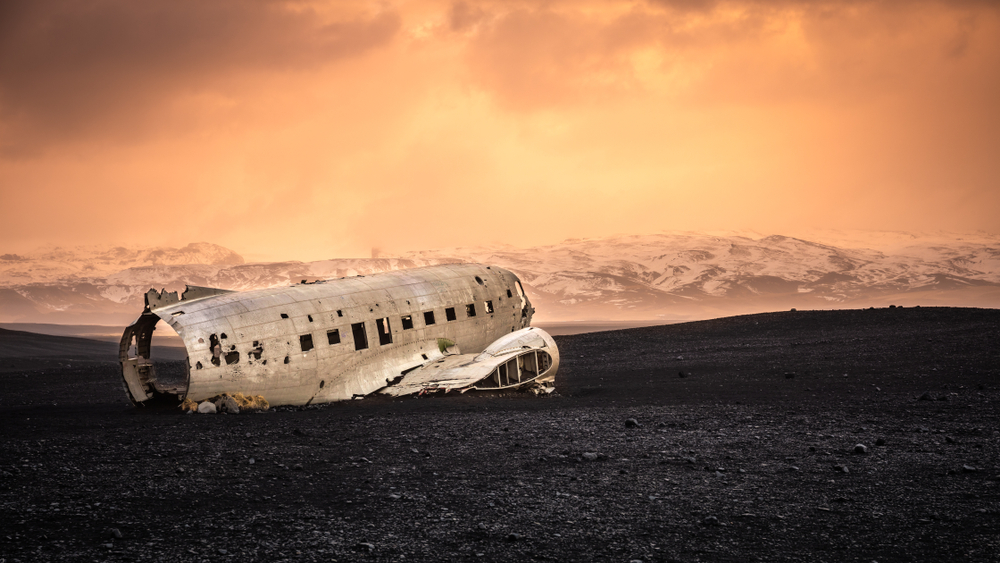 A hollowed out plane from a plane wreck on a black sand beach. In the distance you can see mountains covered in snow. The sky is a orange and yellow shade and looks hazy.