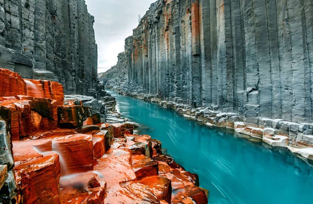 Looking down a rocky canyon in Iceland. The rock columns are a gray color with orange iron stones throughout it. Running through the canyon is a crystal blue river. One of the best stops on an Iceland road trip