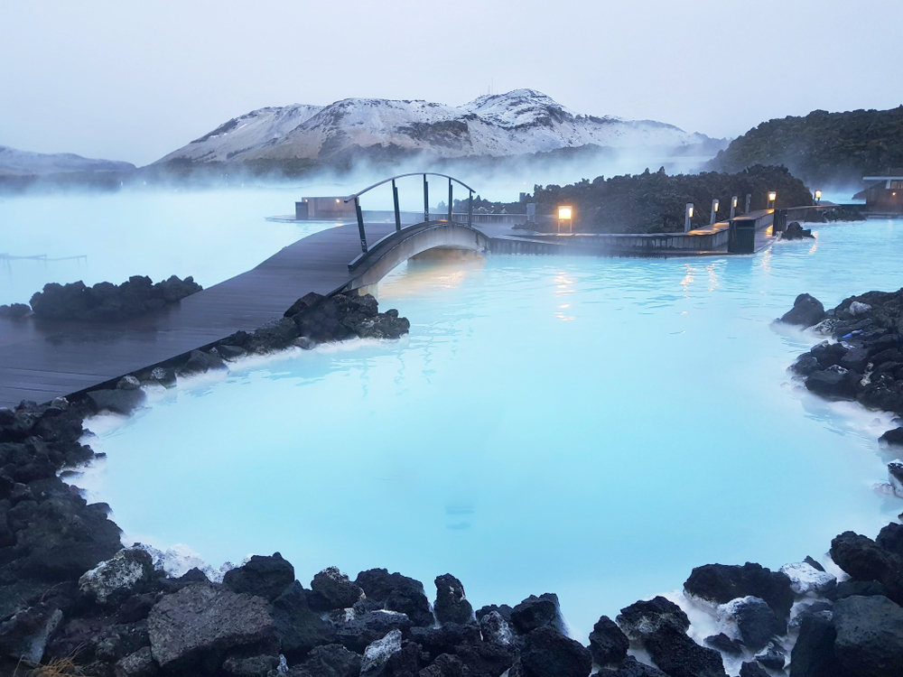 A bridge and walk way with a black railing. It goes over a turquois blue lagoon and there are some black rocks near it. There are lights that light up a path and in the distance is a mountain peak covered in snow.