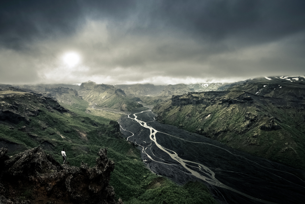 An aerial view of a rocky canyon with a volcanic river bed running through it. It is a dark and moody image with the canyon covered in dark moss and grass and the sky is cloudy.