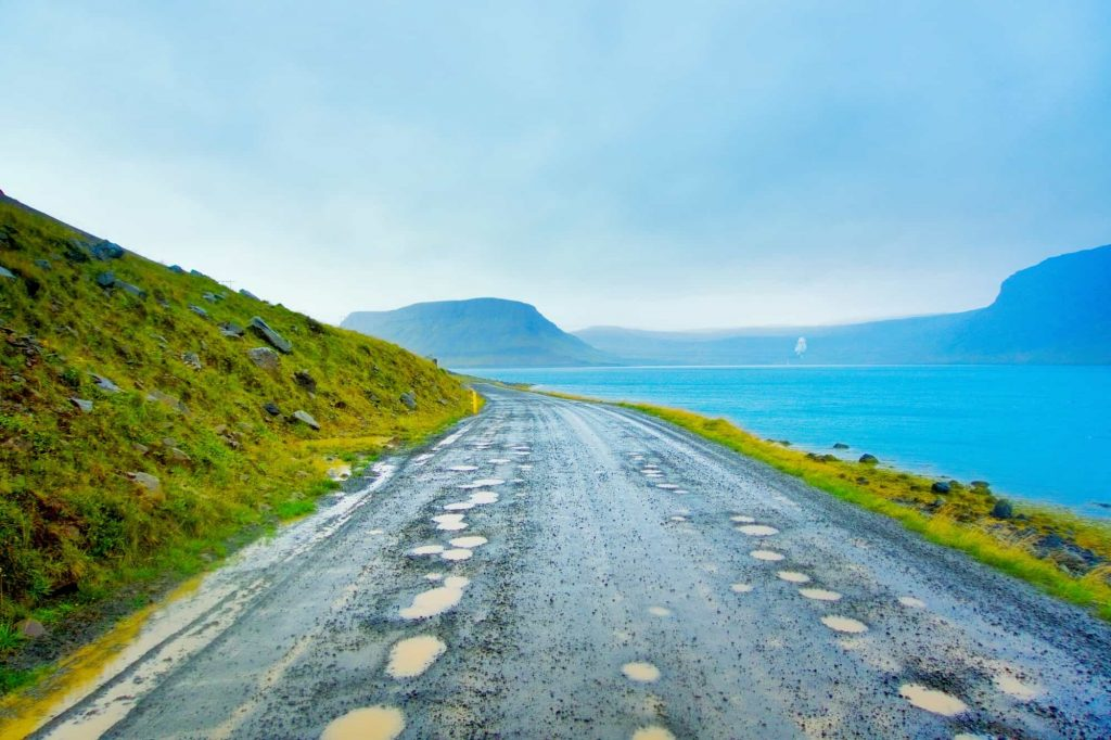 road with pot holes on a moody day in iceland in the WestFjords