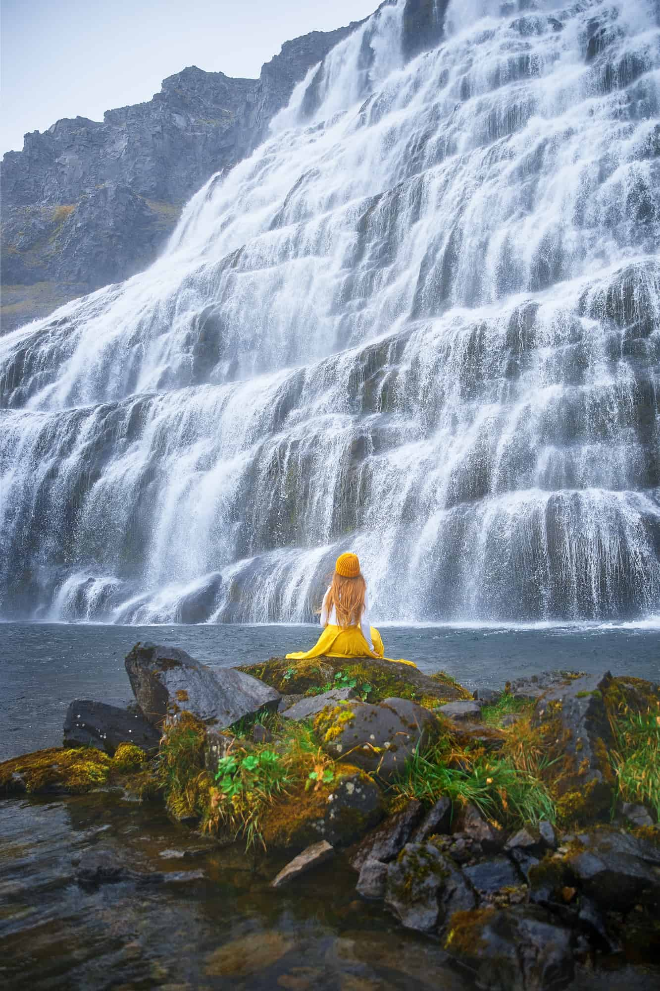 woman sitting in front of Dynjandi Waterfall in Iceland Westfjords