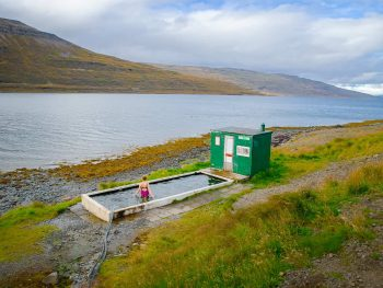 woman sitting in remote hot spring in the Westfjords Iceland