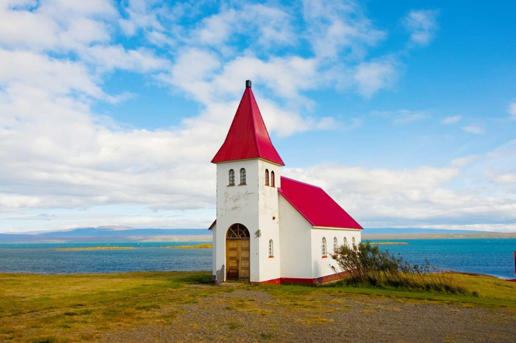 Cute little red church in iceland on a sunny day with blue skies