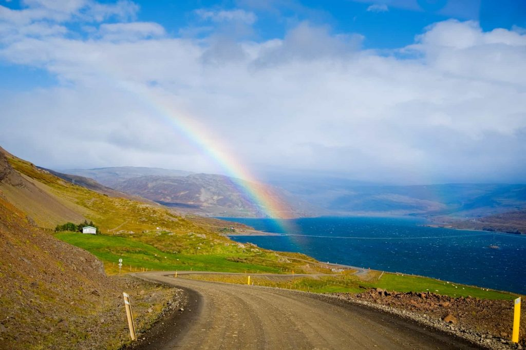 dirt road in the westfjords of Iceland on a sunny day with a rainbow above