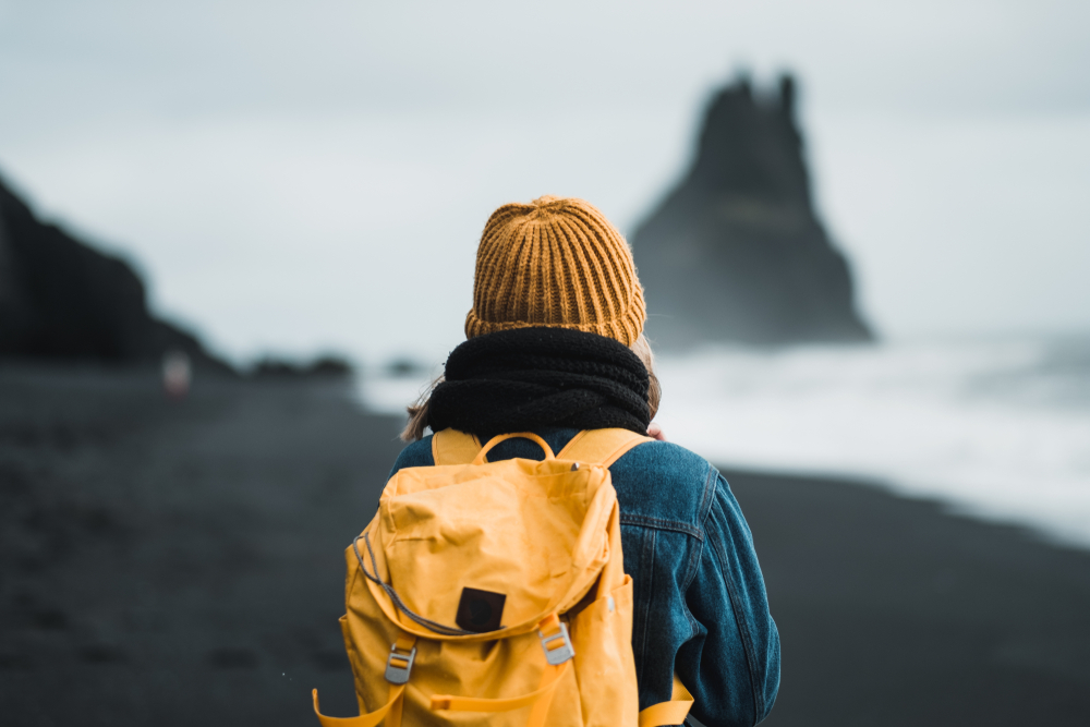 What to wear in Iceland| Woman wearing a yellow beanie, jean jacket and yellow back pack on a black sand beach looking at the ocean