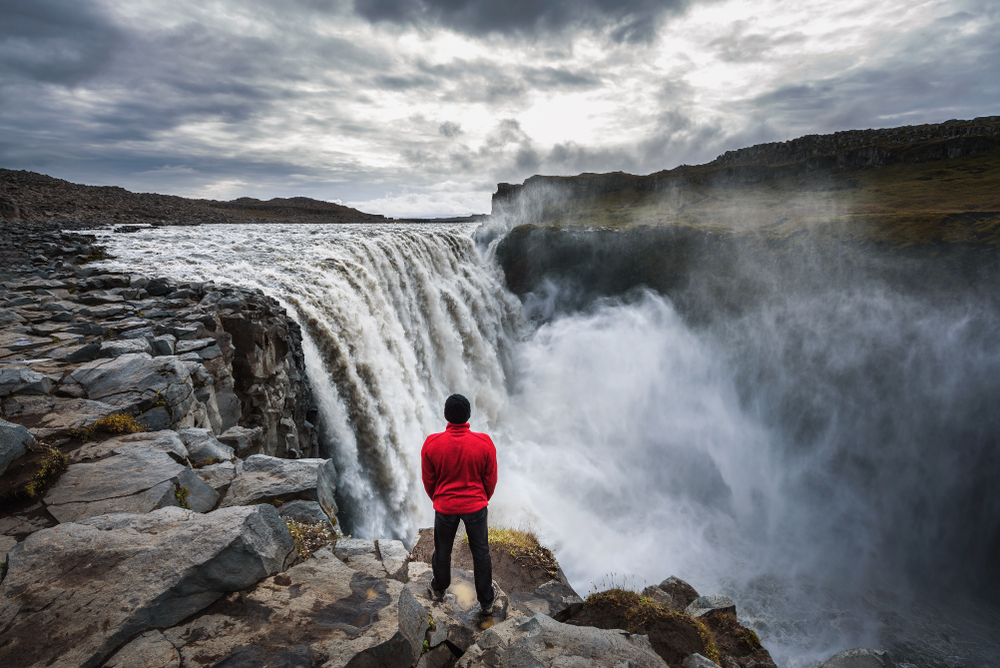a man in a red jacket, black pants and black hat standing at the edge of a large waterfall with mist rising on a cloudy evening during spring in iceland
