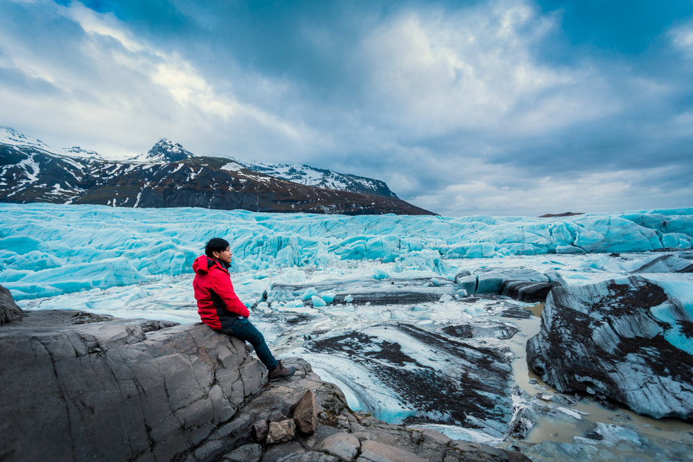man in a red jacket and jeans sitting on a ledge looking out with a large glacier, mountains, and ice chunks behind him on a moody day