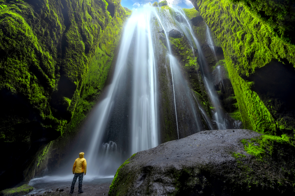 A person in a yellow jacket from their Iceland packing list looking up at a waterfall in a cave