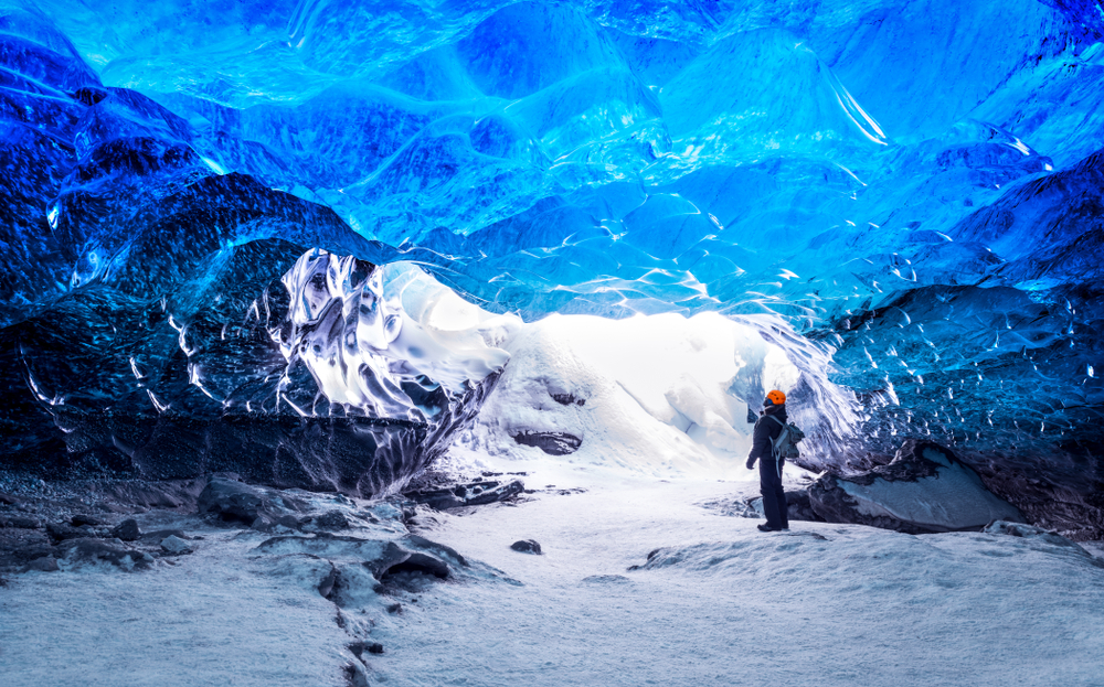 a person standing in an ice cave looking up at thick blue shiny ice in what to wear in iceland for winter