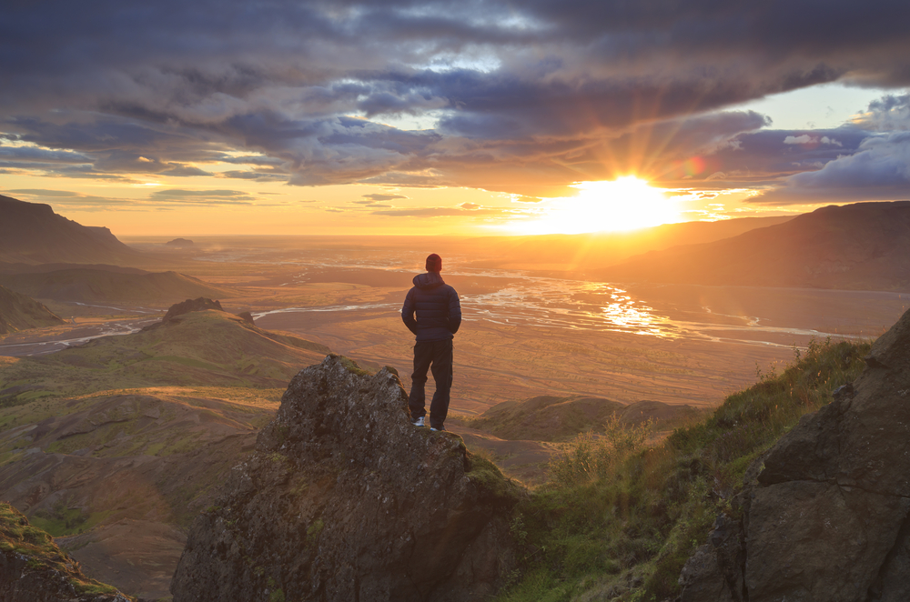 man standing on rock at sunset looking at the vast landscape below dressed in comfortable clothes from his iceland packing list