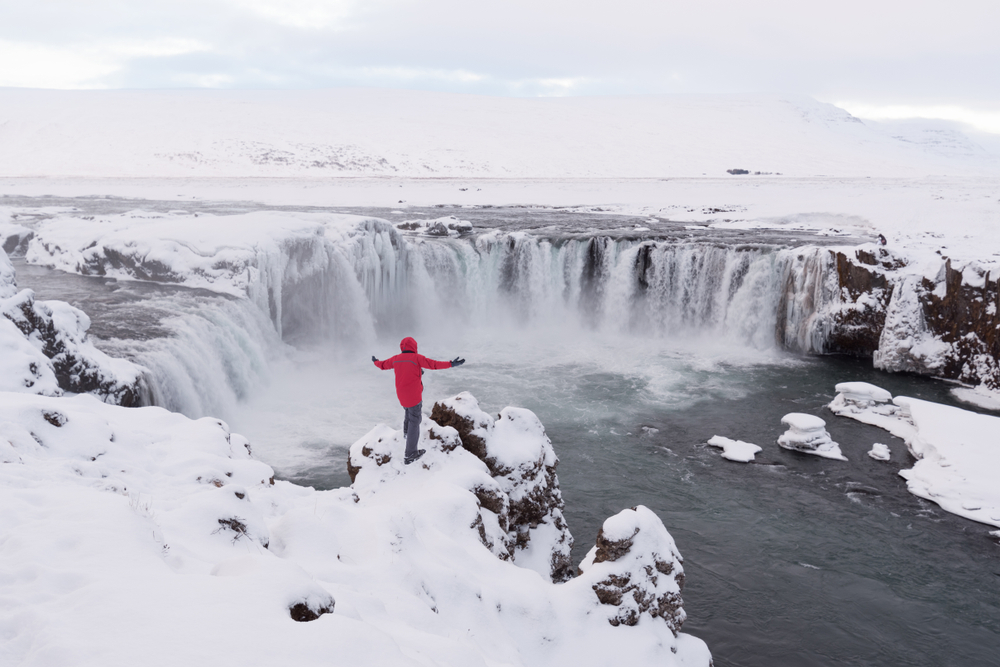 man standing on a snowy ledge with his arms spread out looking at a waterfall on a cloudy winter day