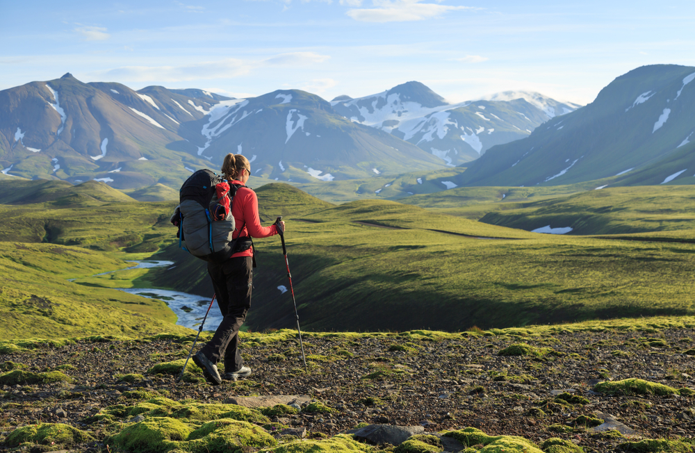 Woman in a red jacket, hiking pants, and a large backpack hiking with walking sticks, on green terrain towards snow covered mountains on a sunny day